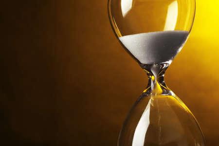 暗い黄色の背景上に砂時計