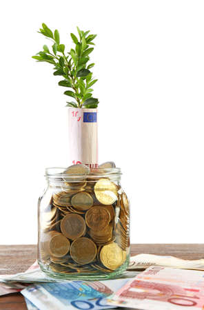 economic botany: Money with growing sprout in glass jar on table isolated on white