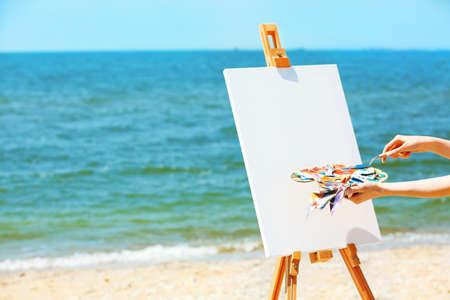 Tavolozza della tenuta della mano femminile con le pitture ed il cavalletto con tela sulla spiaggia