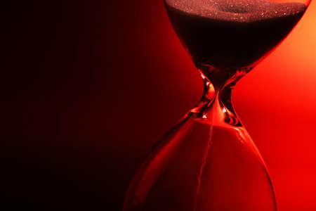 dark red: Hourglass on dark red background Stock Photo