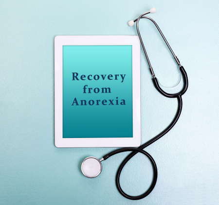 gastroenterology: Tablet pc and text Recovery from Anorexia on screen on light blue background Stock Photo