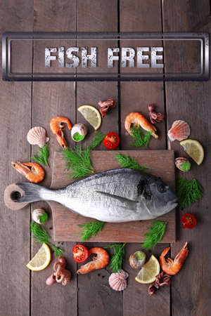 dorado fish: Dorado fish and other ingredients and fish free sign on wooden table, top view Stock Photo