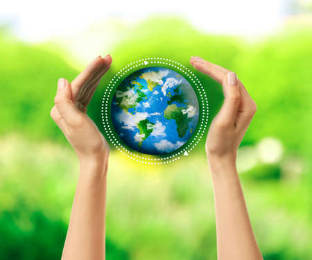Woman holding globe in her hands on nature green background 免版税图像