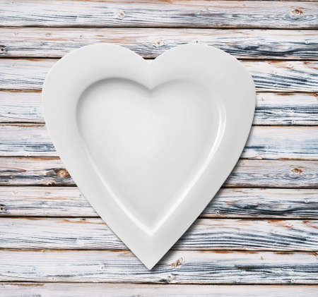 ceramic heart: Plate in shape of heart on wooden background
