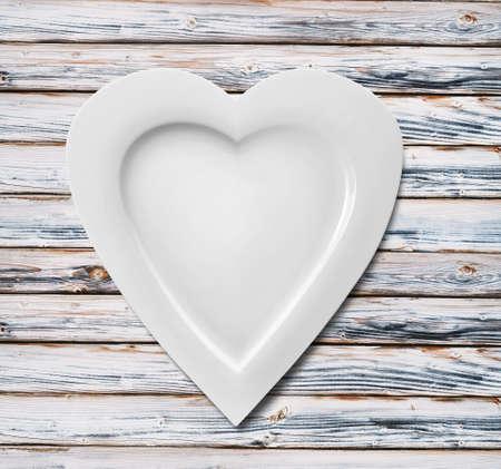 Platte in Form von Herzen auf Holzuntergrund Standard-Bild - 54039595