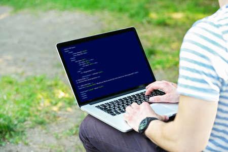 programer: Man using laptop, writing programming code on laptop