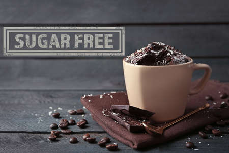 allergic ingredients: Chocolate fondant cake in cup and sugar free sign on wooden background Stock Photo
