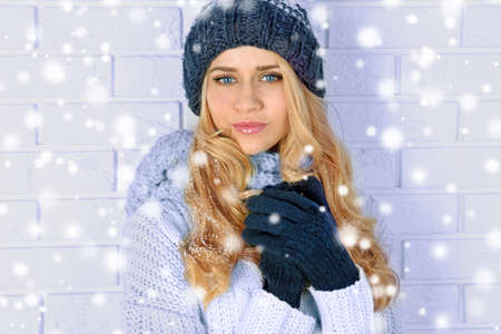 Winter portrait of young beautiful blond woman in her knitted warm clothing. Snowy effect