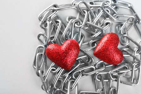 heavy heart: Two red hearts with metal chain, closeup
