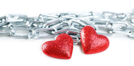 heavy heart: Two red hearts with metal chain isolated on white