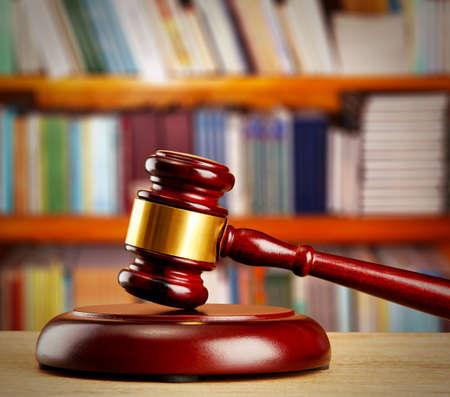 gavel: Judge gavel on wooden table on book shelves background