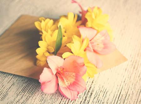 alstroemeria: Pink alstroemeria in envelope on wooden background