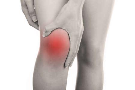 Giovane donna con il dolore al ginocchio isolato su bianco