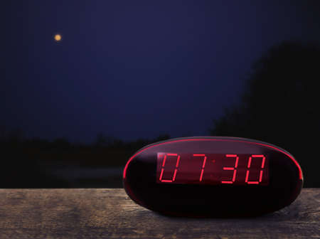 Digital clock showing 7:30 oclock on wooden table, night background