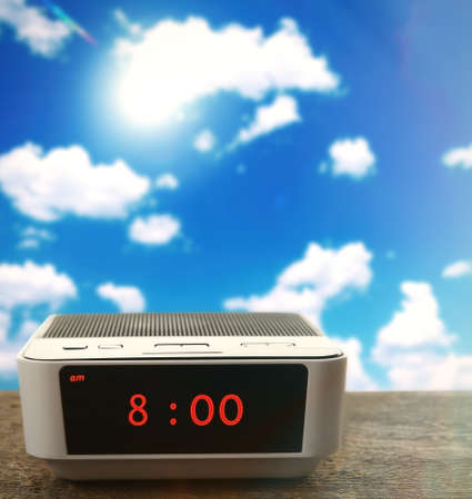Digital clock showing 8:00 oclock on wooden table,  blue sky background