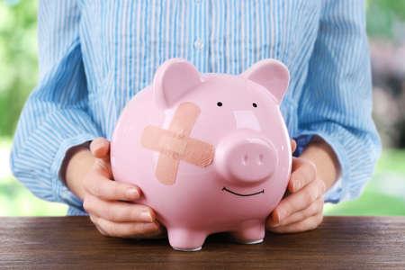 adhesive bandage: Woman holding Piggy Bank with adhesive bandage, on bright background
