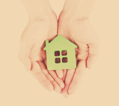 green background: Female hands with model of house on light background Stock Photo