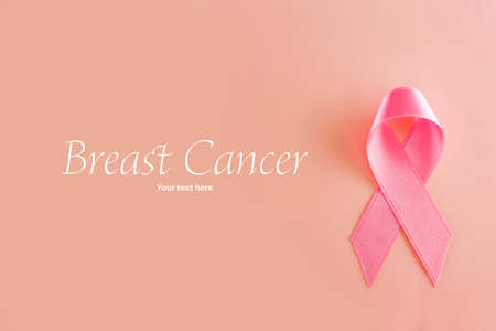 cancer ribbons: Satin ribbon sign on pink background