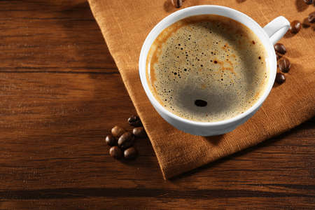 brewed: Cup of fresh coffee with beans on table, closeup