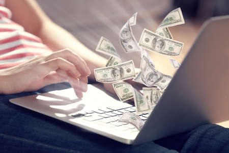 dinero: Concepto financiero. Ganar dinero en Internet. Mujer sentada en el suelo y trabajar con un ordenador portátil