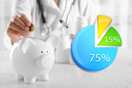 doctor putting money: Business accounting concept. Doctor hands putting coin into piggy bank at table closeup
