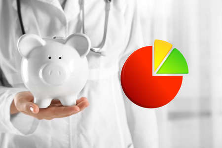 doctor putting money: Business accounting concept. Doctor hands with piggy bank closeup Stock Photo