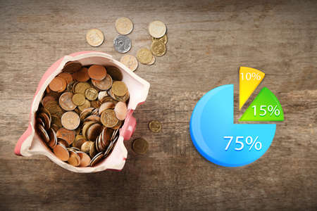 broken trust: Business accounting concept. Broken piggy bank with coins on wooden background