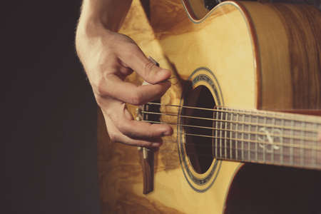 hand jamming: Young man playing on acoustic guitar on dark background