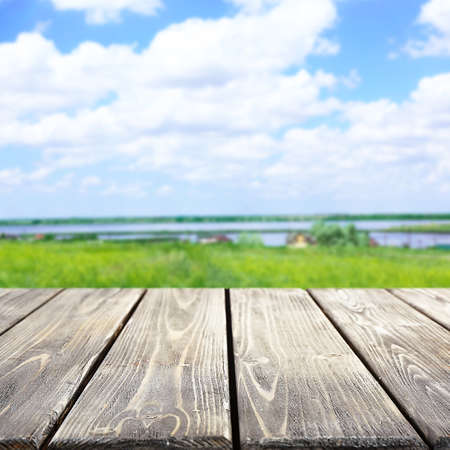 field crop: Wooden table on blurred nature background Stock Photo