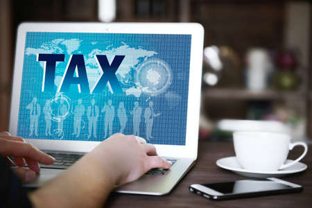 net book: Online Tax payment concept. Womans hands typing on net book at the table, copy space Stock Photo