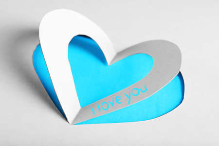cut paper: Cut out white paper heart on blue background