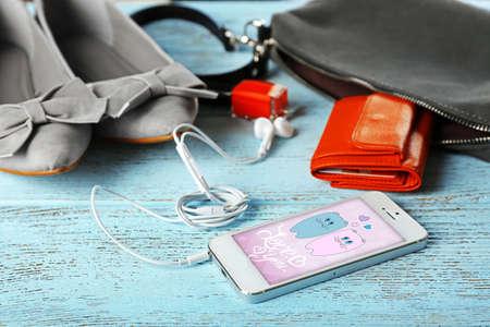 saver: Ladies handbag on wooden background. Smart phone with screen saver