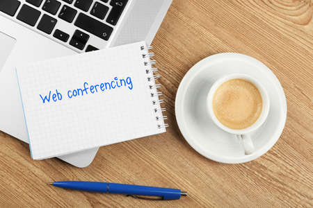 conferencing: Web conferencing written in notebook, laptop and cup of coffee on table, top view Stock Photo