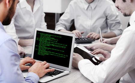 data matrix: Man using laptop, writing programming code on laptop