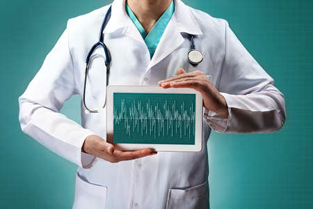 oncologist: doctor holding tablet in hands close-up