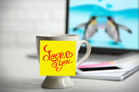 adhesive note: Yellow adhesive note with drawings on coffee cup, on laptop background Stock Photo