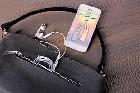screen savers: Ladies handbag on wooden background. Smart phone with screen saver
