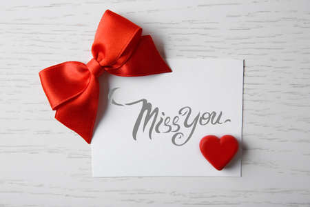 happening: Blank present card with ribbon bow and small heart on wooden background Stock Photo