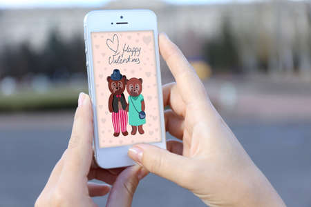 l hand: Woman holding smartphone with screensaver outside