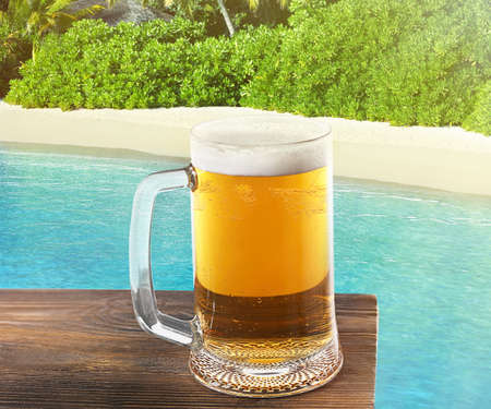 glass cup: Mug of cold fresh beer on table, on sea or ocean background Stock Photo