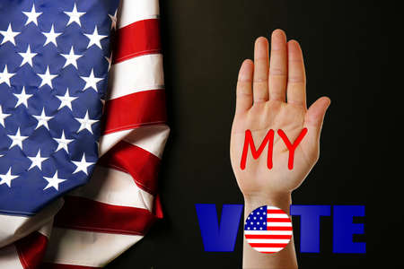 electioneering: Male hand with text My Vote and USA National Flag on black background