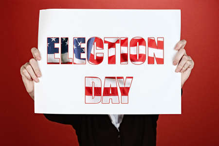 electioneering: Woman holding paper with Election Day text on red background Stock Photo