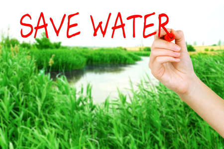 escapement: Female hand with felt-tip pen and Save Water text on lake background
