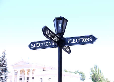 electioneering: Street sign arrow with Elections words on it on city background