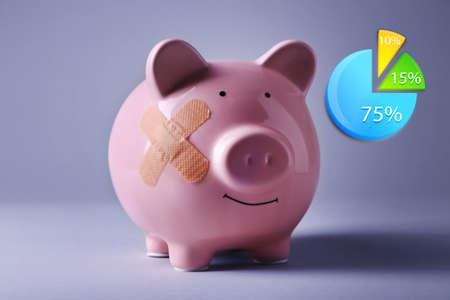 adhesive bandage: Business accounting concept. Piggy Bank with adhesive bandage on grey background Stock Photo