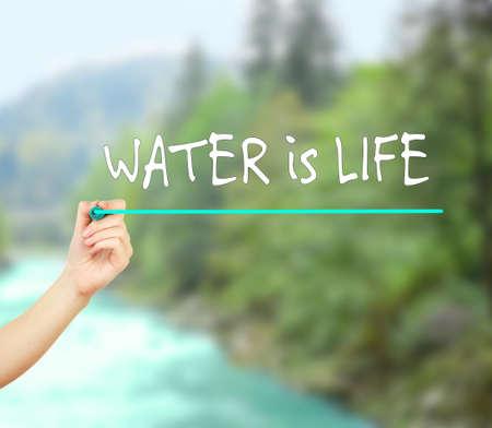 Sparen water concept. Water is Life tekst en met de hand met teller op onscherpe natuurlijke achtergrond