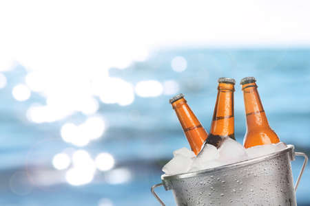 beer bucket: Beer bottles of cold fresh beer in ice bucket, on sea or ocean background