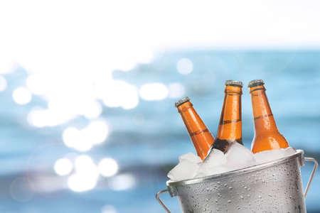 Bottiglie di birra di birra fresca fredda nel secchio di ghiaccio, sul mare o oceano sfondo