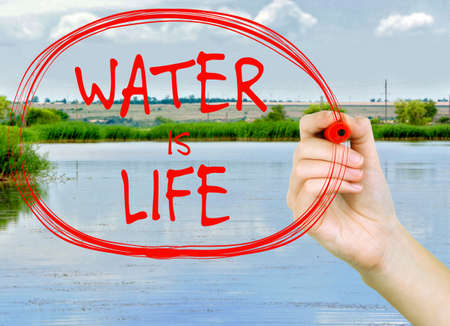 escapement: Female hand with felt-tip pen and Water is Life text on lake background