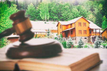decree: Gavel and book on wooden table on building background. Auction concept